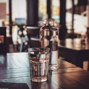 A cup and bottle of water on a wooden table