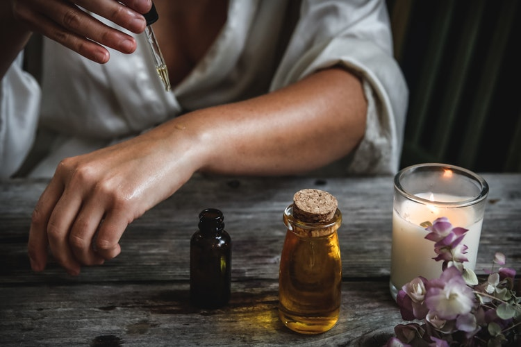 A woman in a white robe putting oils on her skin