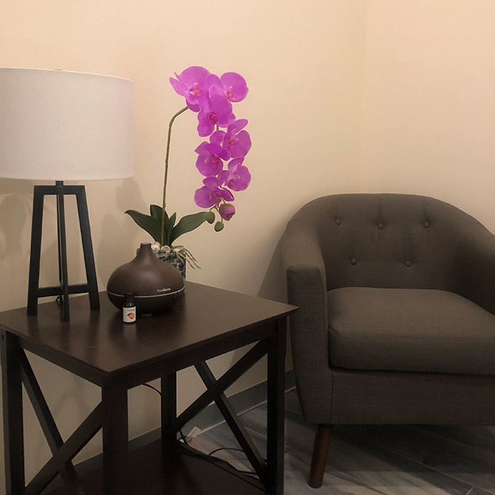 A chair next to a table, lamp, and flower